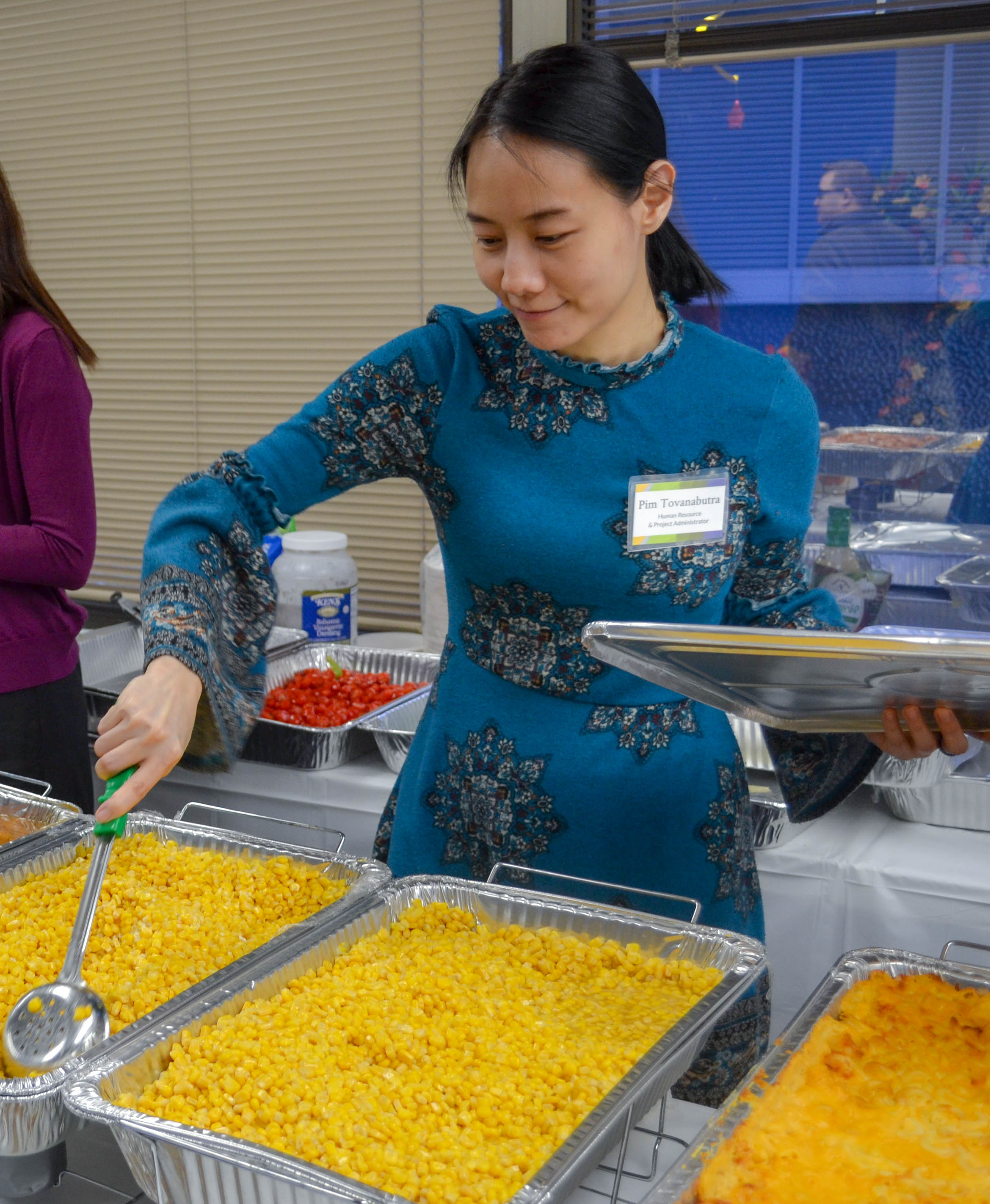 Staff member serves corn at DLS Thanksgiving celebration 2018